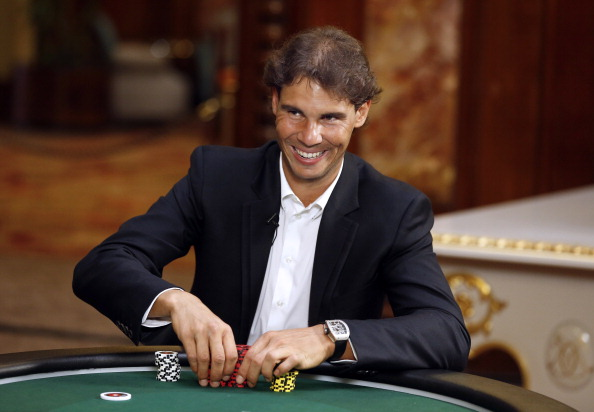 Spain's tennis champion Rafael Nadal smiles as he plays a poker match with the worlds number one female poker player at the Monte-Carlo Casino on April 11, 2014 in Monaco.  AFP PHOTO / VALERY HACHE        (Photo credit should read VALERY HACHE/AFP/Getty Images)