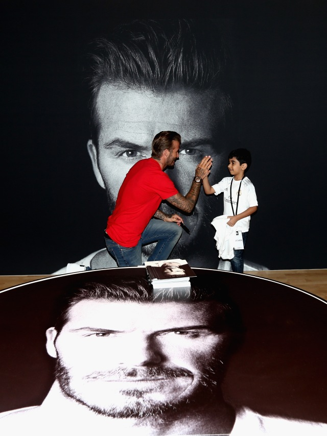 DUBAI, UNITED ARAB EMIRATES - SEPTEMBER 29:  Global icon and footballing legend David Beckham high fives a fan as he opened the new adidas HomeCourt concept store in the Mall of Emirates, Dubai to the delight of thousands of fans who caught a glimpse of the sporting superstar during a whistle-stop visit to the United Arab Emirates on September 29, 2015 in Dubai, United Arab Emirates.  (Photo by Warren Little/Getty Images) *** Local Caption *** David Beckham