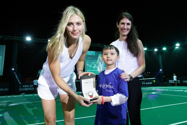 SINGAPORE - OCTOBER 22: Eight-year-old Joshua Ong (C), who suffers from non-Hodgkin lymphoma presents a TAG Heuer limited edition SG50 Aquaracer?to Maria Sharapova (L) as Amelia Sillard, VP, TAG Heuer South East Asia looks on during the Maria Sharapova Exhibition Match at Clifford Pier, Fullerton Bay Hotel on October 22, 2015 in Singapore. (Photo by Suhaimi Abdullah/Getty Images For TAG Heuer) *** Local Caption *** Maria Sharapova; Amelia Sillard; Joshua Ong