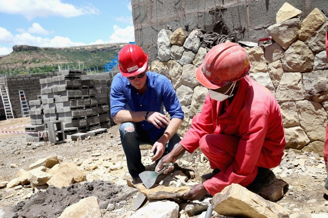 MASERU, LESOTHO - DECEMBER 10: Prince Harry helps with sandstone cladding for the guardhouse as he visits the construction site for the new Sentebale Mamohato Children's Centre at Thaba-Bosiu on December 10, 2014 in Maseru, Lesotho. Prince Harry was visiting Lesotho to see the work of his charity Sentebale. Sentebale provides healthcare and education to vulnerable children in Lesotho, Southern Africa. The particular theme of his visit was to check on the progress of the Mamohato Children's Centre which will provide vital support to children affected by HIV. Prince Harry founded Sentebale (which means 'Forget Me Not' in Sesotho) with Prince Seeiso in 2006. (Photo by Chris Jackson/Getty Images) *** Local Caption *** Prince Harry